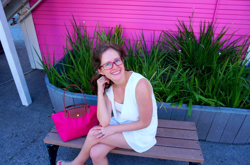 pink-purse-woman-white-outfit-glasses